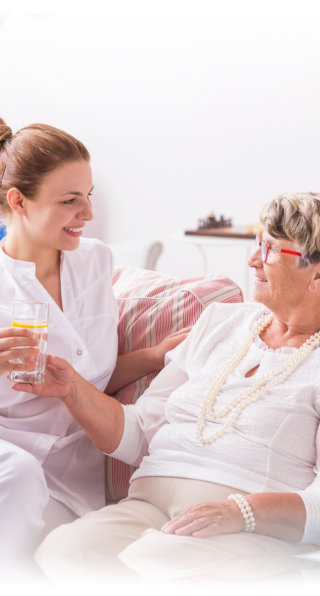 nurse talking to an elderly woman in bed